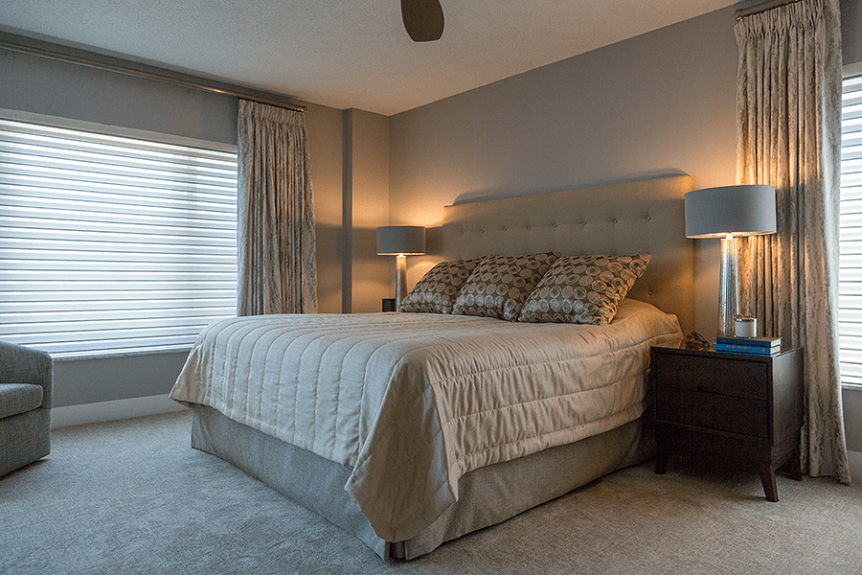 bedroom with neutral tones of coverlets and pillows