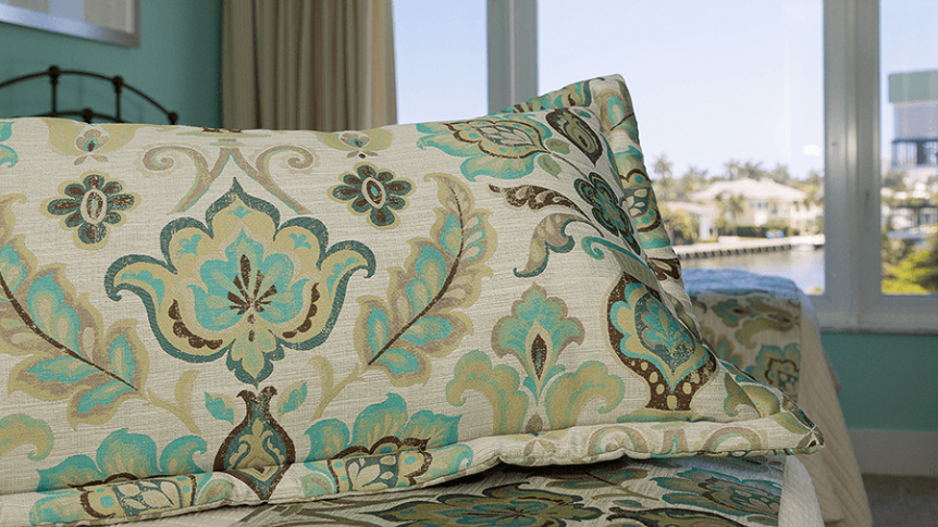 custom upholstered pillow for sofa in aqua and gold toned print