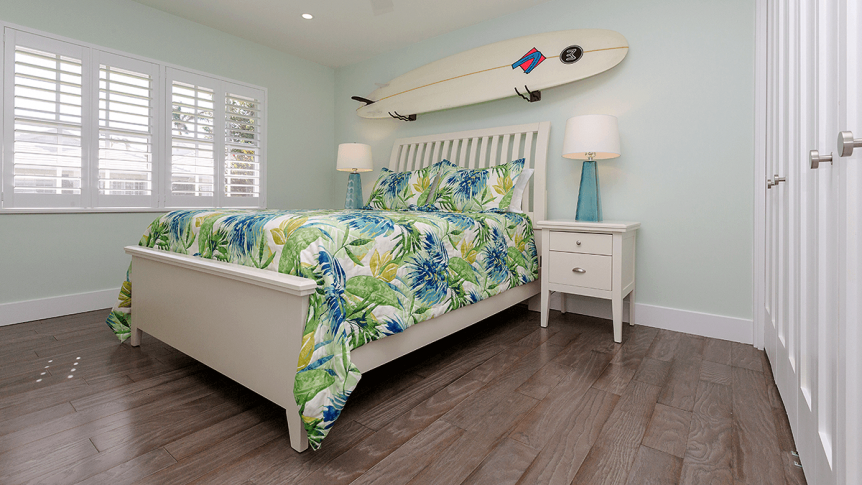 beachy bedroom with a surfboard above headboard