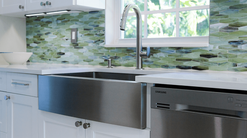 kitchen sink with green glass tile backsplash