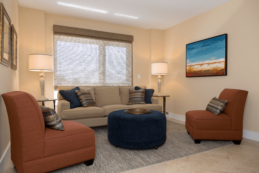 den with neutral colored sofa and brick colored sofa chairs