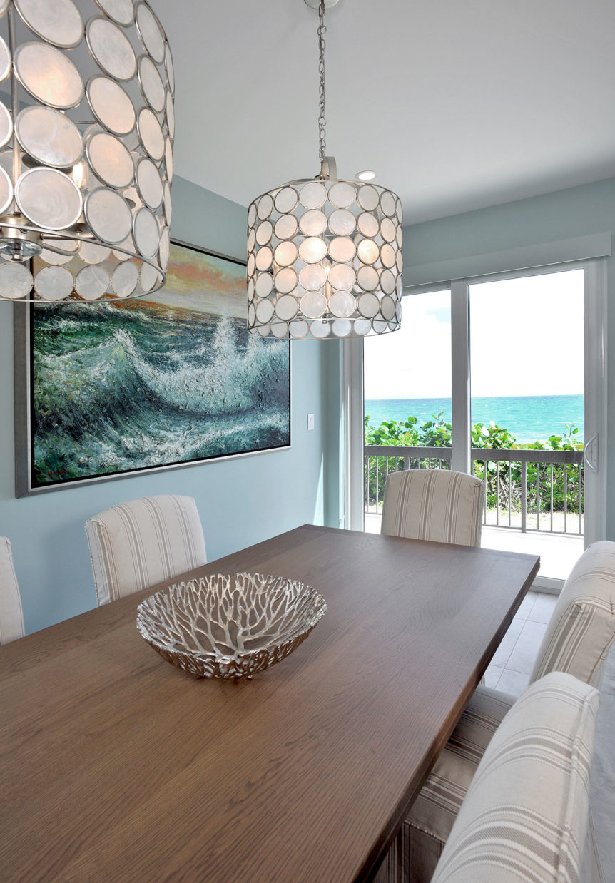 Capiz shell light pendants had over a long dining table in a beach house