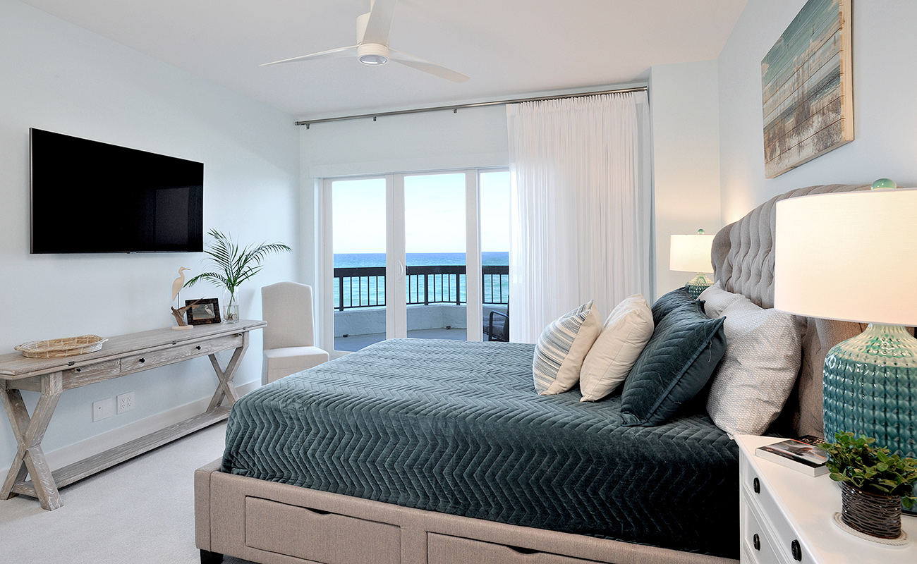 Guest bedroom of a beach house in Florida designed in sea blues, beige and white, with an ocean view
