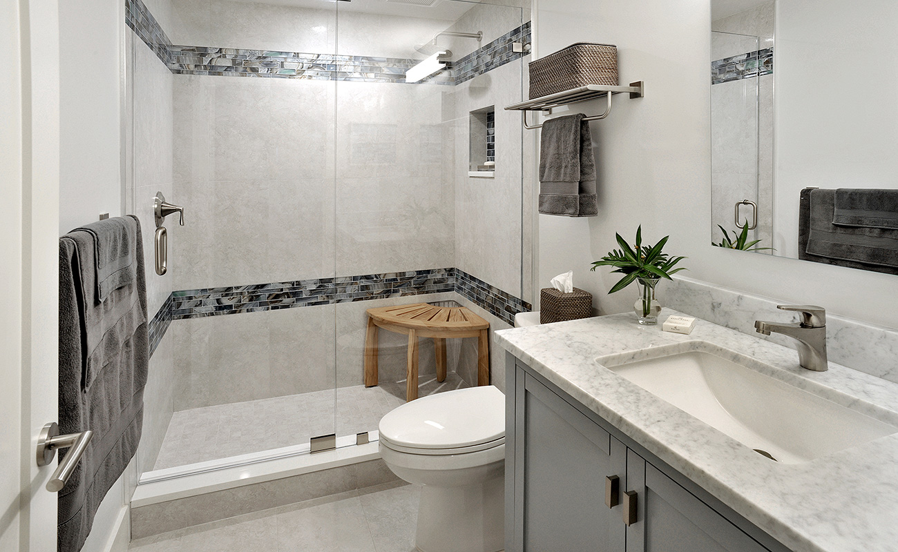 Guest bathroom with simple fixtures and tile borders in the stall in white and gray color palette