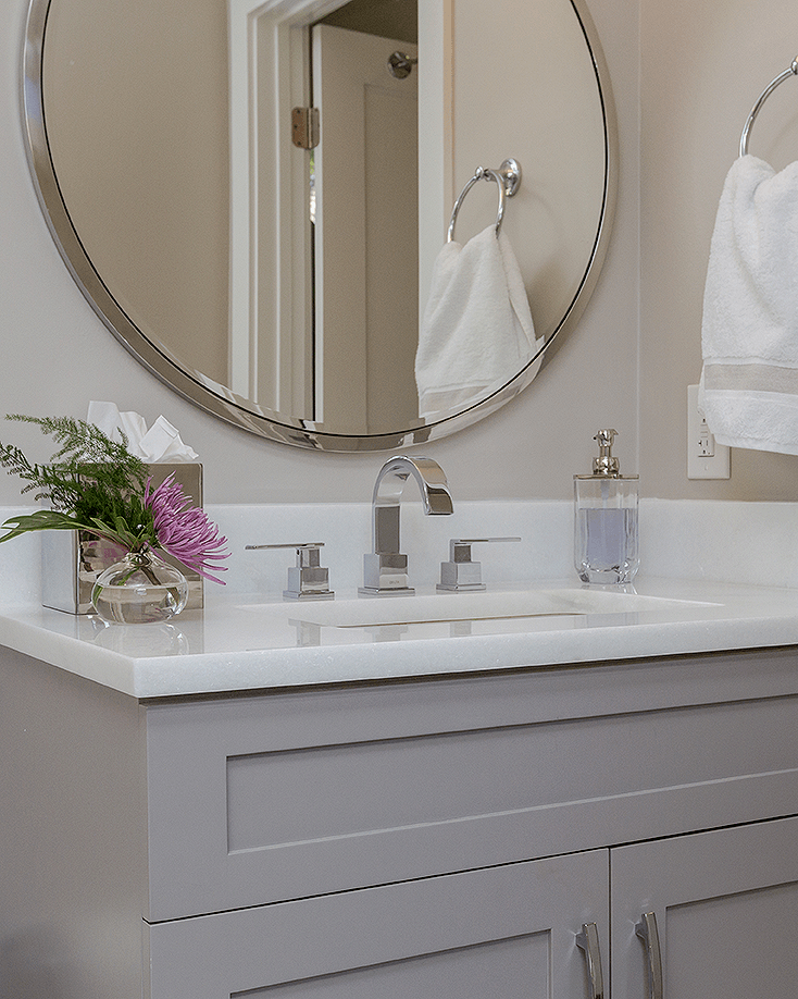 bathroom with shaker cabinets and round mirror