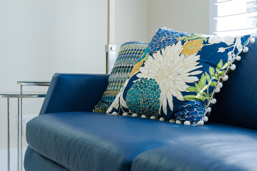 deep blue sofa with bright colored floral cushion