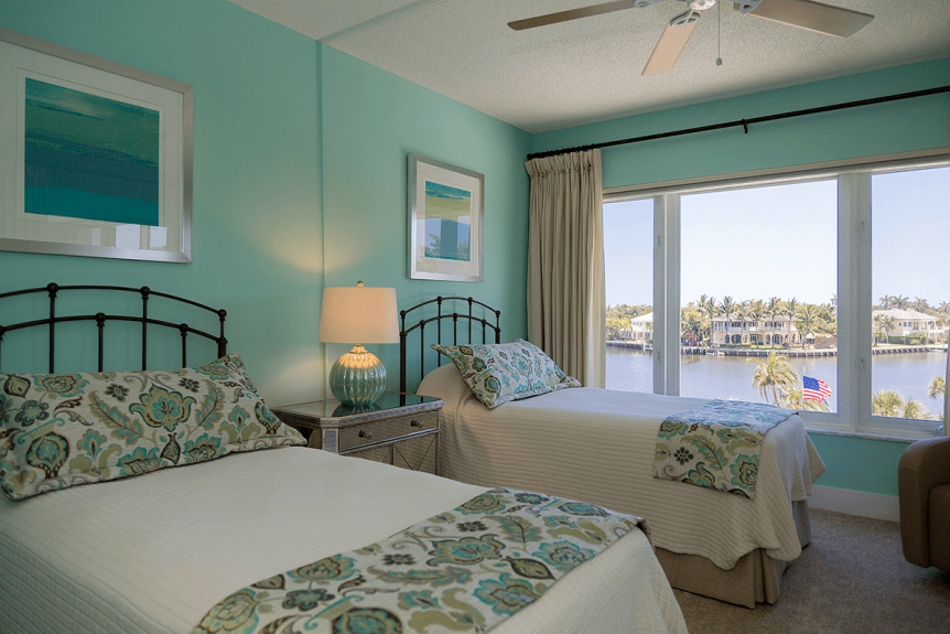 twin beds with aqua bedding in a guest room with waterfront window