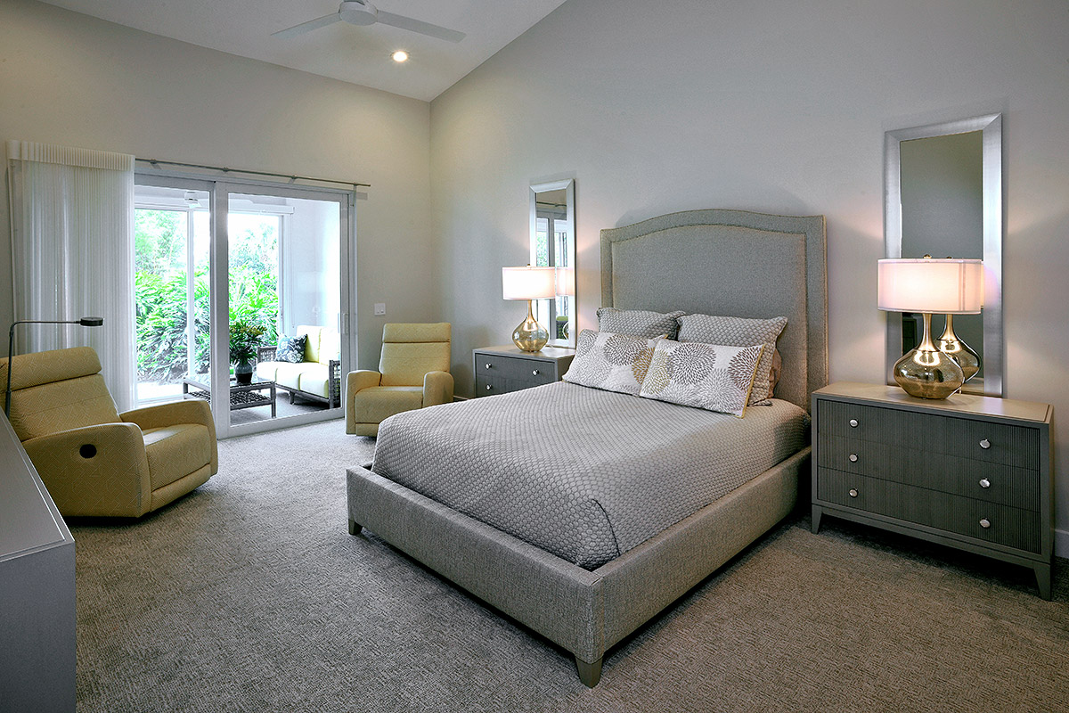 guest room with high fabric headboard and cozy chairs