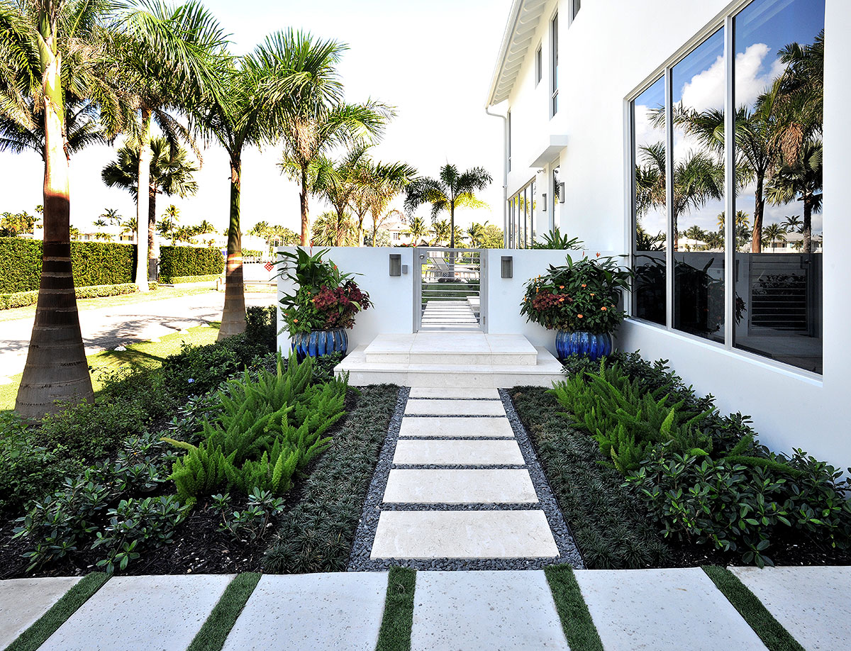 landscaping with square pavers and bed of greens on either side