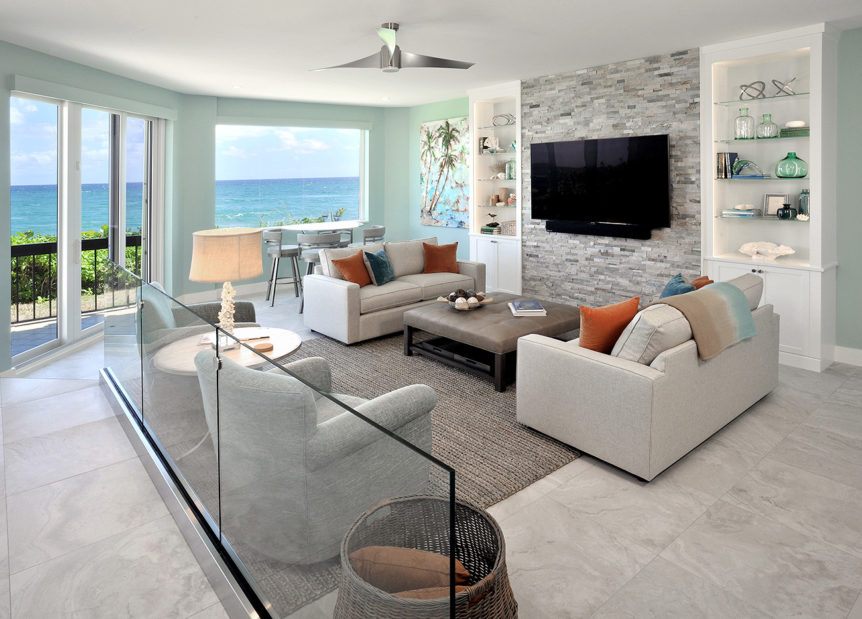 Living room in a beach house with beige sofas and bright coral and blue cushions