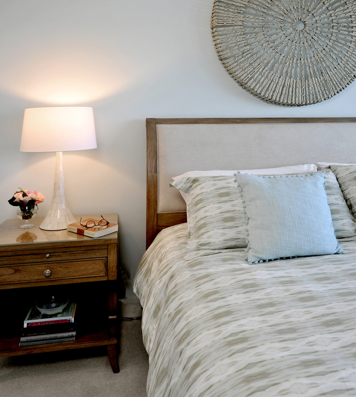 Close up of the beach house bedroom showing rattan wall decoration and capiz lamp on dark wood side table