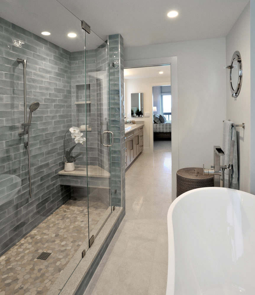 Aqua tiles and natural pebbles in tones of blue and beige are used inside the shower stall
