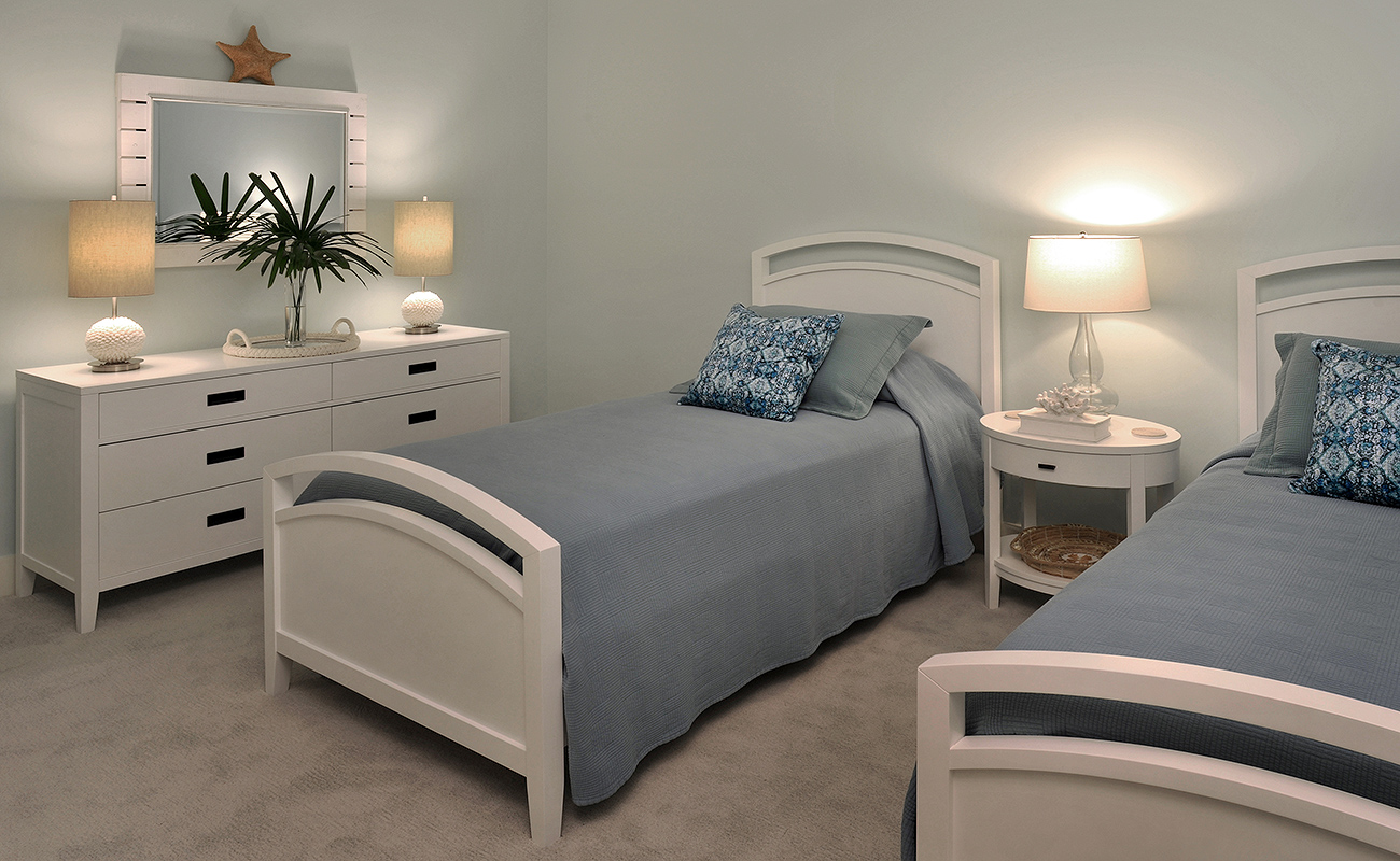 Guest bedroom of a beach house with twin beds designed with a coastal color palette of tonal blues, beige, and white.
